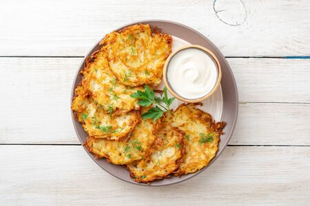 Potato pancakes or latkes or draniki with sour cream in plate on white wooden table. Top view. Copy space.