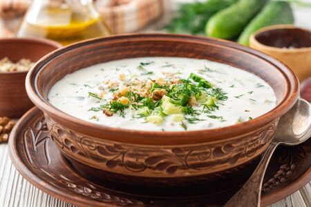 Traditional Bulgarian cold summer soup tarator with yogurt, dill, cucumber and walnuts in ceramic bowl on wooden table.