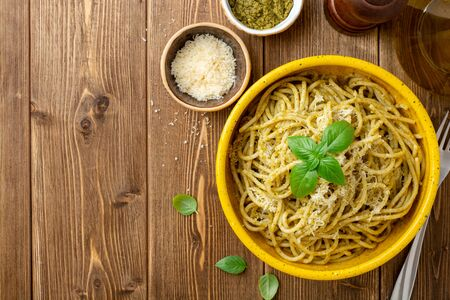 Spaghetti pasta with sauce pesto and parmesan cheese in ceramic bowl on wooden table.