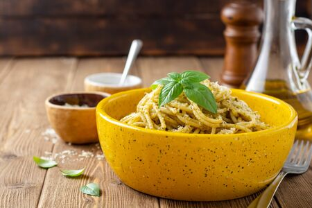 Spaghetti pasta with sauce pesto and parmesan cheese in ceramic bowl on wooden table. Selective focus.