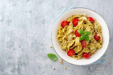 Fettuccine pasta with sauce pesto, cherry tomatoes, pine nuts and parmesan cheese on concrete