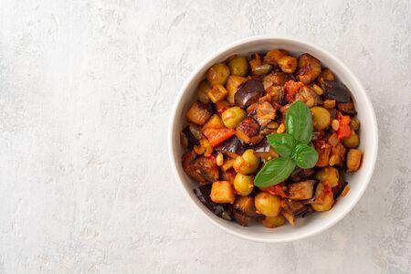 Traditional sicilian eggplant dish Caponata in bowl on concrete Фото со стока