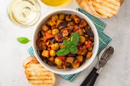 Traditional sicilian eggplant dish Caponata in bowl on concrete