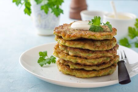 Zucchini fritters with fresh parsley and sour cream in plate on blue concrete background. Selective focus.