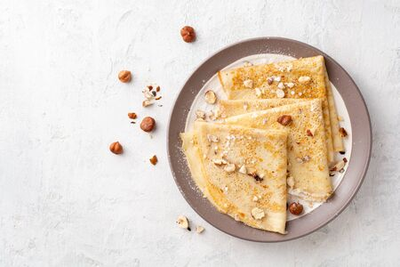 Crepes with hazelnuts and powdered sugar on plate on white concrete Фото со стока