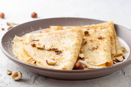 Crepes with hazelnuts and powdered sugar on plate on white concrete background. Selective focus.