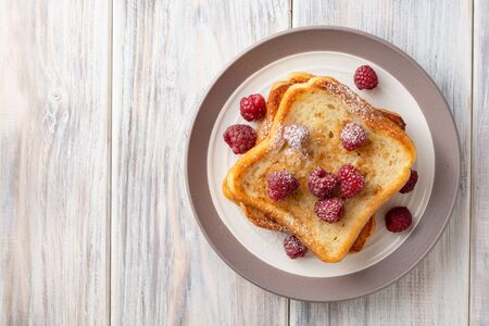 French toasts with powdered sugar and fresh raspberries on wooden table. Top view. Copy space.