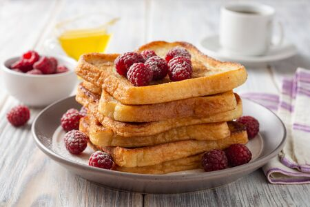 French toasts with powdered sugar and fresh raspberries on wooden table. Selective focus.