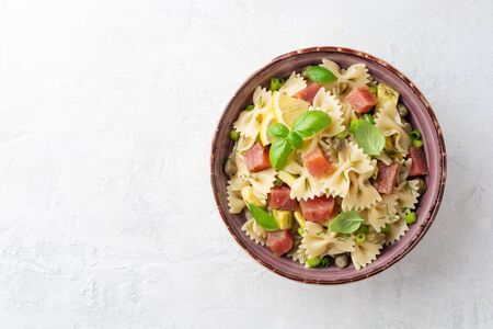 Farfalle pasta salad with smoked tuna, avocado, capers and greens in bowl on concrete background. Top View. Copy space. Фото со стока
