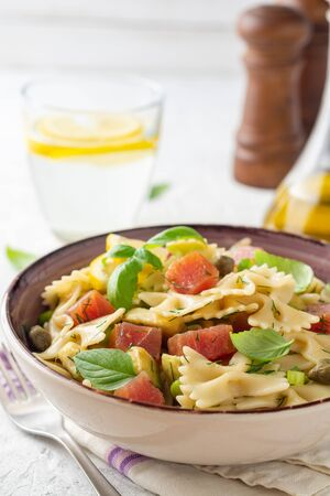 Farfalle pasta salad with smoked tuna, avocado, capers and greens in bowl on concrete background. Selective focus.