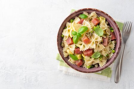 Farfalle pasta salad with smoked tuna, avocado, capers and greens in bowl on concrete