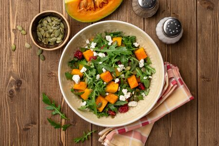 Autumn salad with baked pumpkin, arugula, seeds, dried cranberries and feta cheese in bowl on rustic wooden background. Top view. Фото со стока