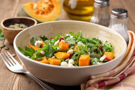 Autumn salad with baked pumpkin, arugula, seeds, dried cranberries and feta cheese in bowl on rustic wooden background. Selective focus.