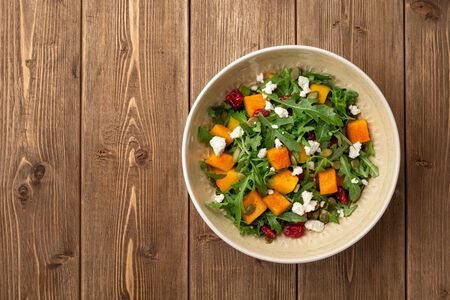 Autumn salad with baked pumpkin, arugula, seeds, dried cranberries and feta cheese in bowl on rustic wooden background. Top view. Copy space. Фото со стока