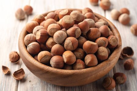 Hazelnuts in bowl on white wooden background. Selective focus. Stockfoto