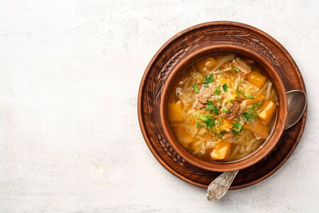 Traditional russian cabbage soup with turnip shchi in ceramic bowl on concrete background. Top view, copy space. Stock Photo