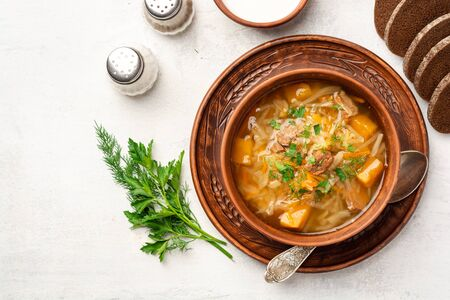 Traditional russian cabbage soup with turnip shchi in ceramic bowl on concrete background. Top view.