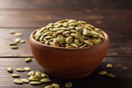 Pumpkin seeds in ceramic bowl on dark wooden