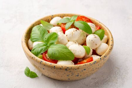 Traditional Italian caprese salad with mozzarella cheese, cherry tomatoes and basil in ceramic bowl on concrete background. Selective focus.