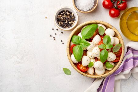 Traditional Italian caprese salad with mozzarella cheese, cherry tomatoes and basil in ceramic bowl on concrete background. Top view, copy space. Archivio Fotografico