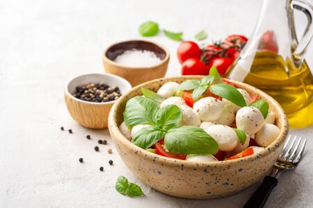 Traditional Italian caprese salad with mozzarella cheese, cherry tomatoes and basil in ceramic bowl on concrete Archivio Fotografico