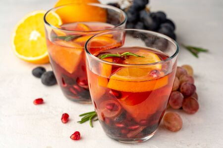 Homemade sangria with orange, grapes and pomegranate seeds in glasses on concrete background. Selective focus.