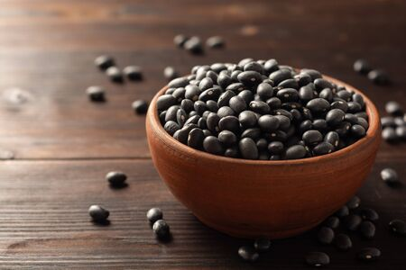Black beans in ceramic bowl on dark wooden