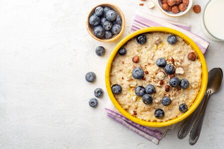 Oatmeal porridge with hazelnuts and blueberries in bowl on concrete background. Top view, copy space. Archivio Fotografico