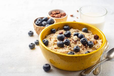 Oatmeal porridge with hazelnuts and blueberries in bowl on concrete background. Selective focus.