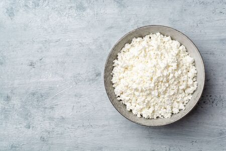Cottage cheese in bowl on concrete background. Top view, copy space.