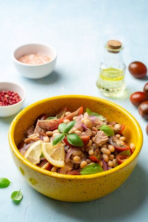 Healthy salad with tuna, white beans, cherry tomatoes, red onion and basil leaves in ceramic bowl on concrete background. Selective focus.