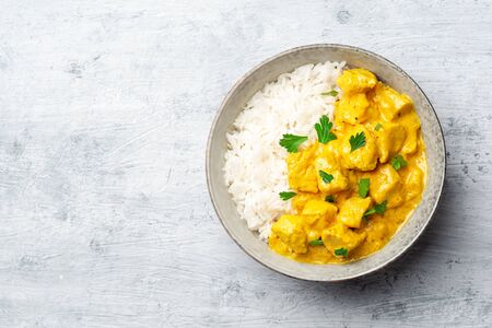 Chicken curry with rice and parsley in bowl on concrete background. Top view, copy space.