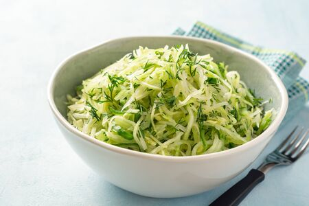 Fresh cabbage and cucumber salad with dill in bowl on concrete background. Coleslaw. Selective focus.