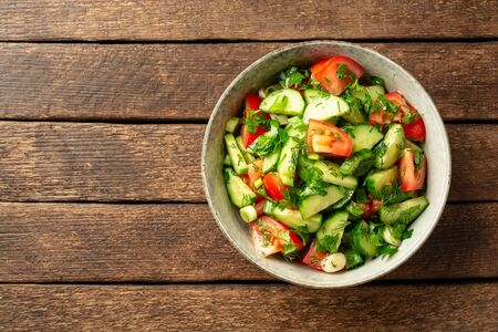 Fresh vegetable salad with cucumber, tomato and greens in bowl on rustic wooden table. Top view, copy space. Reklamní fotografie
