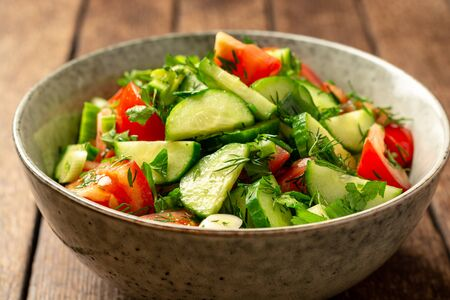 Fresh vegetable salad with cucumber, tomato and greens in bowl on rustic wooden table. Selective focus.