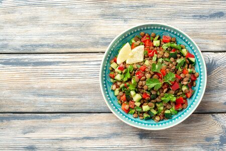 Lentil salad with cucumber, bell pepper and coriander leaves on rustic wooden table. Top view, copy space. Standard-Bild - 149964429