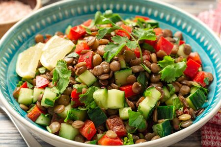 Lentil salad with cucumber, bell pepper and coriander leaves on rustic wooden table.