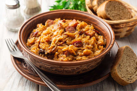 Traditional Polish dish Bigos in ceramic bowl on rustic wooden table. Selective focus. Reklamní fotografie