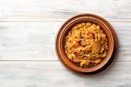 Traditional Polish dish Bigos in ceramic bowl on rustic wooden table. Top view, copy space.