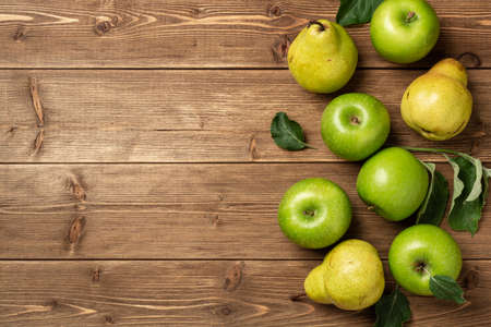 Fresh green apples and pears on rustic wooden background. Top view, copy space.