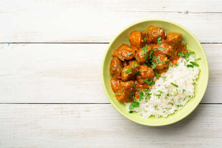 Meat stew with white rice on rustic wooden background. Top view, copy space. Reklamní fotografie