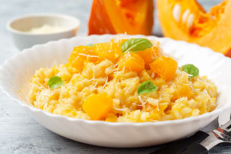 Pumpkin risotto with parmesan cheese and basil leaves on concrete background. Selective focus.