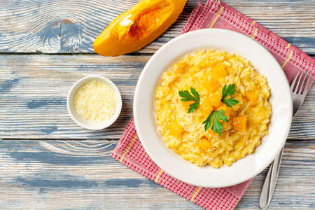Pumpkin risotto with parmesan cheese and parsley in plate on wooden background. Top view, copy space.