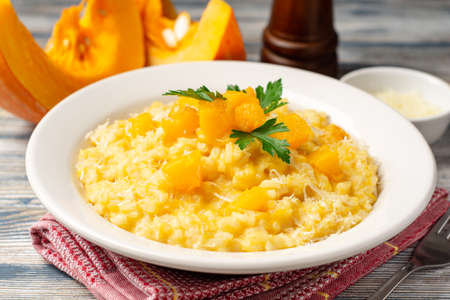 Pumpkin risotto with parmesan cheese and parsley in plate on wooden background. Selective focus.