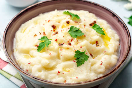 Mashed cauliflower with butter, pink peppercorns and parsley on concrete background. Selective focus.
