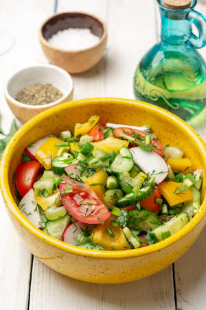 Fresh vegetables salad with radish, cucumber, bell pepper, tomato, celery and greens in ceramic bowl on white wooden rustic background. Selective focus.
