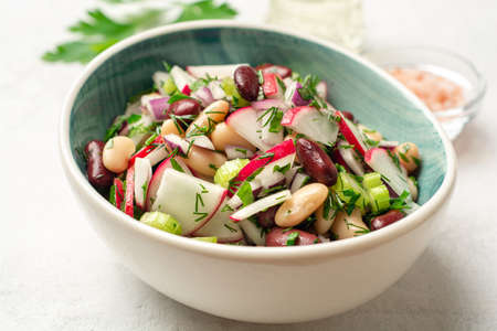 Vegetable salad with radish, celery, red onion, beans and greens in bowl on concrete background. Selective focus.