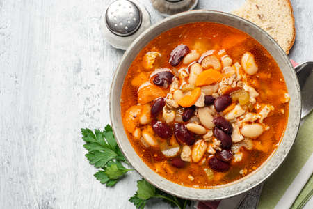 Bean soup with bacon, carrot, celery and onion in bowl on concrete background. Top view, copy space.