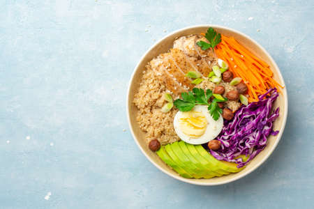Healthy buddha bowl with quinoa, chicken, egg, avocado, carrot, red cabbage, hazelnuts and greens