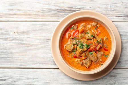 Traditional hungarian paprikash with turkey, bell pepper, carrot, onion, paprika and sour cream in bowl Standard-Bild